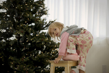 Portrait of a young girl climbing a stool next to a Christmas tree.