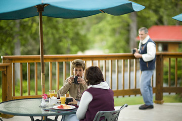 Mature adult woman and a mid-adult female having breakfast on a deck.