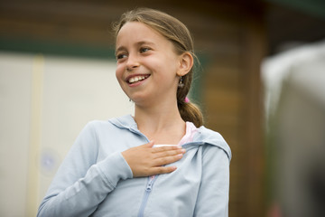 Smiling young girl with her hand to her chest.