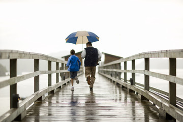 Young boy running along a jetty with his father as he holds an umbrella.