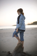 Girl standing on a bit of driftwood along a beach.