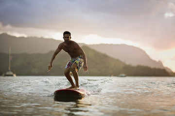 Male surfer starting to stand as his surfboard moves forward.