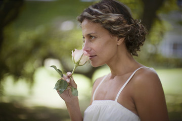 Portrait of an attractive woman smelling a rose.