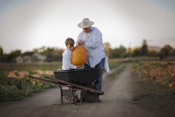 Father and his son lifting a pumpkin into a wheelbarrow.