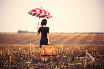 young woman with suitcase and umbrella