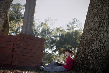 Young boy sitting against a tree trunk wearing a hat.