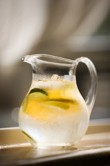 Iced water in a jug with lemon and lime slices.