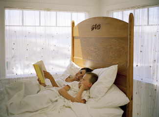 Mature woman reading stories to her son in bed.