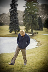 Mid-adult man walking with his hands in his pockets around a golf course.
