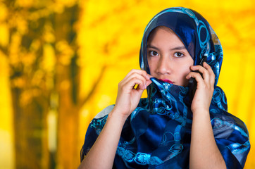 Beautiful young muslim woman wearing blue colored hijab, facing camera posing mysteriously, autumn forest background
