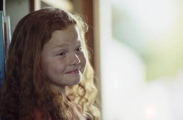 Smiling young girl with red curly hair and freckles.