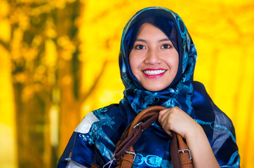 Beautiful young muslim woman wearing blue colored hijab, holding leather purse, facing camera posing happily, autumn forest background