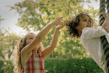 Young girl gesturing while her friend plays on a rope swing.
