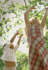 Two young girls dancing in the sun with their arms raised.