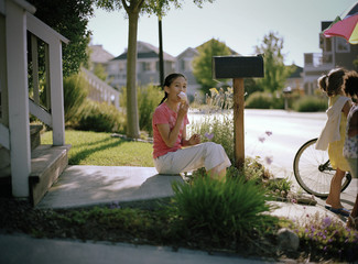 Portrait of teenage girl sitting by her letterbox eating an ice cream.