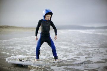 Young boy wearing a helmet and wetsuit while standing on a surfboard.