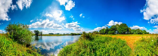 Wall Mural - Landschaft mit Fluss, Feldern und Bäumen bei blauen Himmel und Sonnenschein