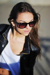 Young beautiful brunette girl in white shirt and leather jacket sunbathing near the water. Wearing sunglasses. Outside