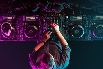 Charismatic disc jockey at the turntable. DJ plays on the best, famous CD players at nightclub during party. EDM, party concept.
