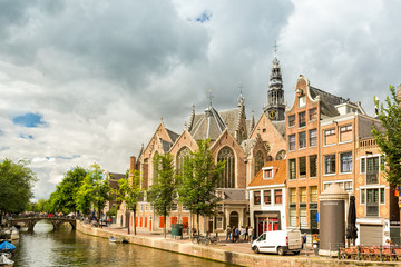Fototapete - Amsterdam Red Light District canal with the Old Church (aka De Oude Kerk) among typical dutch houses, on a sunny summer morning
