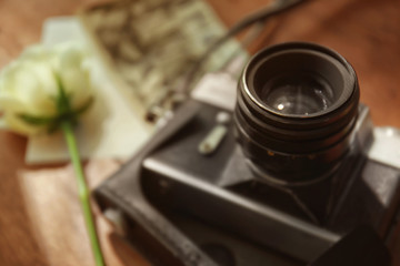 Vintage camera, photos and beautiful roses, closeup