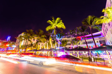 Ocean Drive scene at night with neon lights, palm trees, cars and people having fun, Miami beach.