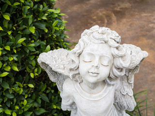 White Cherub sculpture with wings and closing eyes