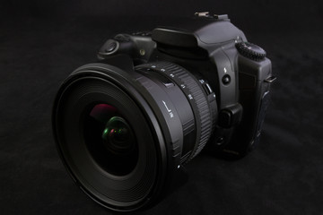 One black camera with wide angle lens isolated on black backgrou