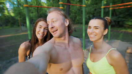 fitness, sport, friendship, technology and healthy lifestyle concept - group of happy friends taking selfie outdoors.