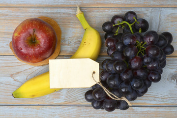 Organic fresh fruit, apple, banana, grapes with a empty copy space label tag on a wooden background