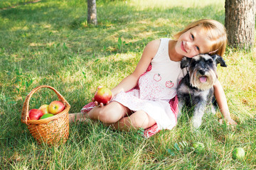 Cute little girl sitting on the grass in the garden with the dog