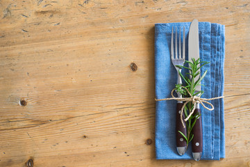 Fork, knife and napkin decorated with rosemary and thyme on wooden rustic background
