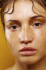Portrait of a beautiful girl on a yellow background with the effect of wet skin