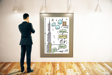 Businessman looking at business sketch