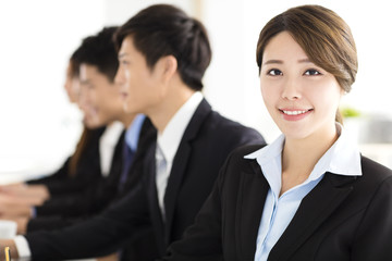 Smiling businesswoman looking at camera with  colleague
