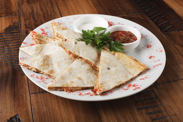 quesadilla with beef and chicken on brown wood table. quesadilla and sauce.
