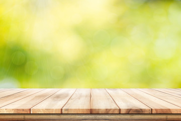 Empty wooden  table with foliage bokeh background. Ready for product display montage.