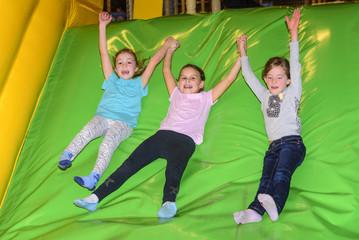 drei Mädchen auf der aufblasbaren Rutsche im Freizeitpark