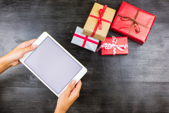 Closeup of Christmas gifts on table with blank tablet