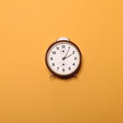 Vintage brown alarm clock on yellow ocher background - Trendy mi