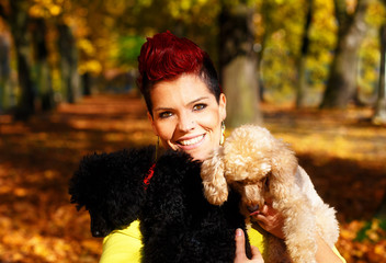 Cute smiling girl with black and white dog and hugging at the autumn park outdoors. Eye contact.