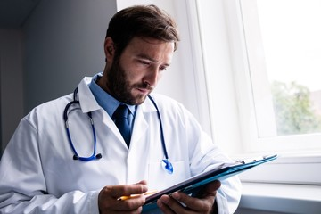 Doctor standing in corridor looking at clipboard