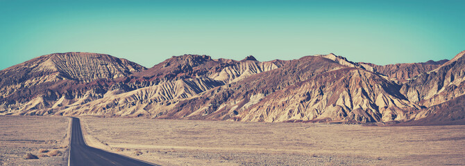 Old film stylized panoramic picture of desert road in Death Valley, travel concept, USA.