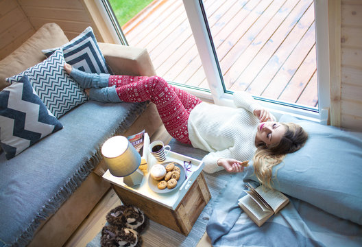 Young beautiful blonde woman with book lying down home by the livingroom window. Lazy cold day off concept