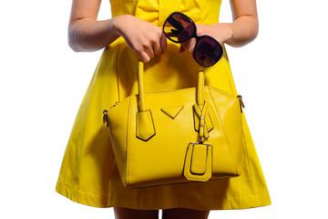 Elegant fashionable woman in yellow dress with handbag and sunglasses