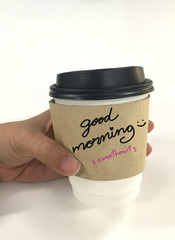 Hand with coffee cup and good morning message