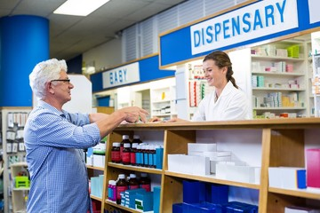 Pharmacist giving prescriptions of medicine to customer