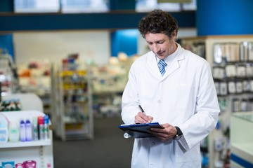 Pharmacist writing on clipboard