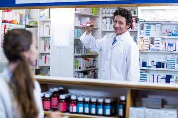 Pharmacist standing at counter and showing medicine box