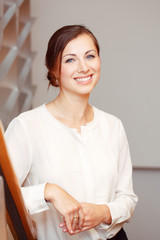 Portrait of beautiful smiling nice young white Caucasian business woman with blue eyes wearing white office blouse shirt dress code, looking in camera, slavic Russian European face